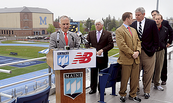 University of Maine President Robert Kennedy (left) speaks during a press conference at the university's Alfond Stadium in Orono announcing a $5 million gift from New Balance toward the renovation of the Memorial Gym and field house. Looking on (from left) are UMaine vice president for student affairs Robert Dana, New Balance director of public affairs Matt LeBretton, and UMaine athletic director Steve Abbott.