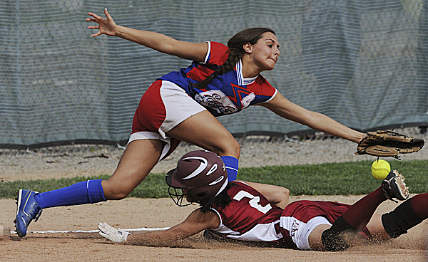 Messalonskee's Amanda Joy reaches for a wide throw as Bangor's Jade Baumrind dives into third base during the second inning of their high school softball game in Bangor on Wednesday. The throw went into the outfield and Baumrind scored, but the Eagles won 9-7.