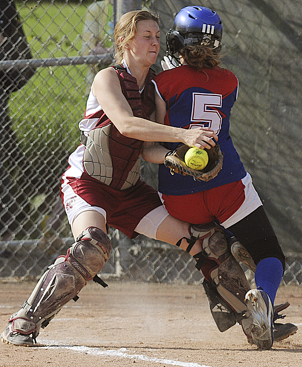 Messalonskee's Bri Garland collides with Bangor catcher Sadie Redman en route to home plate during sixth inning of a high school softball game at Bangor Wednesday. Garland was safe on the play and the Eagles won 9-7.