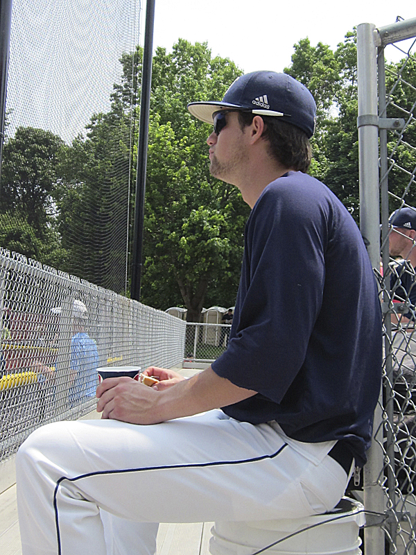 Colin Gay of the University of Maine eats a sandwich while watching the end of Thursday's first game between Albany and Binghamton at the America East Baseball Championship in Stony Brook, N.Y.