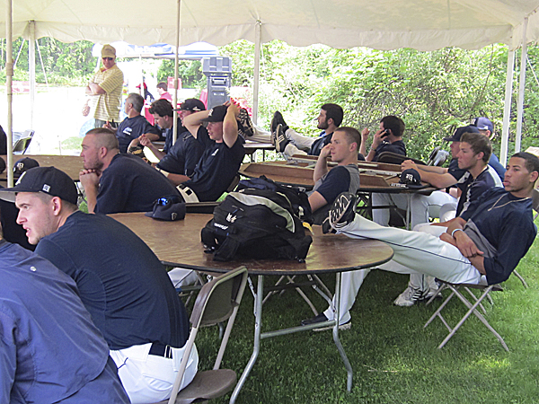 Members of the University of Maine baseball team seek shelter under a tent as they try to escape the hot sun while waiting to play Thursday's game against Stony Brook in the America East Baseball Championship at Joe Nathan Field in Stony Brook, N.Y.