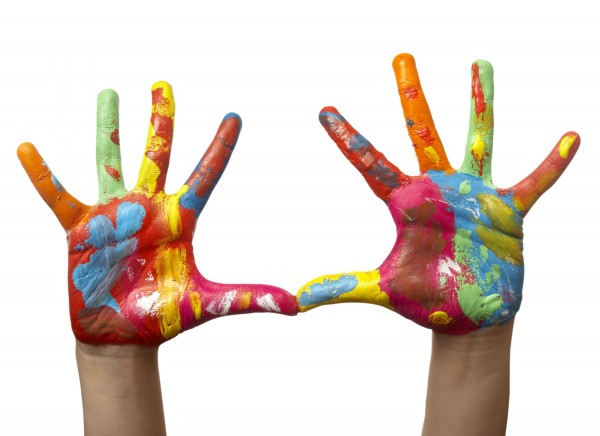 A child's hands covered in finger paint.