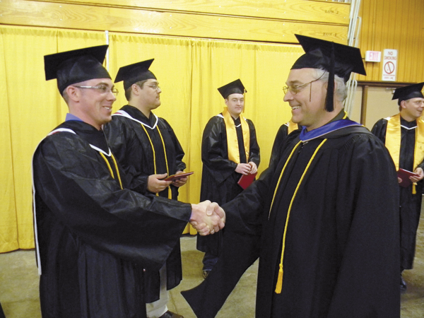 Matthew Melcher (left) of Bingham, Maine, one of the 14 students who is among the first wind power technology graduates from a post-secondary institution in New England, is congratulated by Wayne Kilcollins (right), Northern Maine Community College wind power technology instructor after NMCC commencement exercises at The Forum in Presque Isle on Saturday.