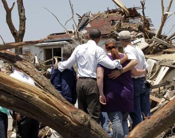 President Barack Obama (second from left) with residents views damage from the tornado that devastated Joplin, Mo., Sunday, May 29, 2011.