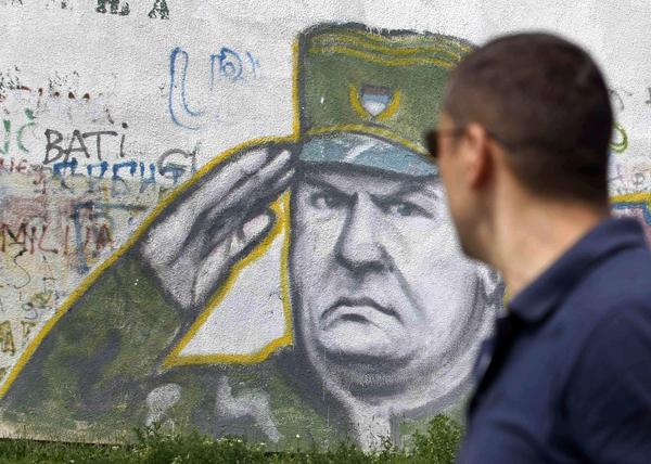 A boy walks pass graffiti of war crimes fugitive Bosnian Serb army commander Ratko Mladic in Belgrade, Serbia, Thursday. Serbia's President Boris Tadic confirms war crimes fugitive Ratko Mladic has been arrested.
