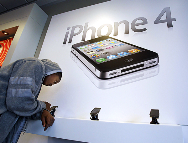 A customer tries an Apple iPhone 4 at a Verizon store in Mountain View, Calif. Apple should have responded much sooner to concerns about location data stored on its iPhones, even if the company didn't have all the answers ready, marketing and crisis-management experts say.