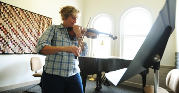 Violin student Joyce Hillman tunes her violin before before a music lesson at  Bay Chamber Music School on Friday, May 15, 2011.