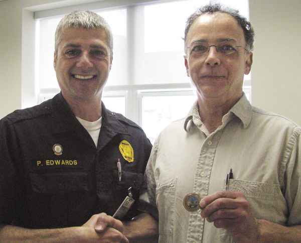 Matt Tilley, a 52 year old Bangor resident was issued a challenge coin by Sgt. Paul Edwards for his efforts to help save a woman who jumped from the Joshua Chamberlain Bridge and into the Penobscot River on April 11, 2011.  Mr. Tilley was at the Sea Dog on Front Street when a person came into the bar asking if anyone had a rope and that someone needed assistance in the river. Mr. Tilley quickly ran to his truck where he thought he had a rope and then upon not finding it, ran for the riverbank. He assisted Officer Angelo and other unknown passerby's to drag the woman from the river to dry ground.  In a letter issued by Chief Ron Gastia to Matt Tilley he writes, &quotyour selflessness in assisting Officer Angelo to remove the woman from water are most certainly appreciated, and are commendable.&quot Chief Gastia adds, &quotAs the Chief of Police, it is both refreshing and reassuring to know that people, like you, are willing to get involved in order to help the police in their efforts to keep citizens and visitors safe.  Your actions dictate that you are deserving of the Bangor Police Department's Challenge Coin.&quot
