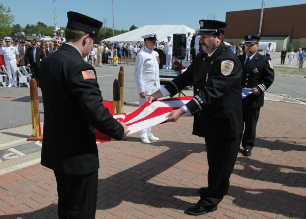 Brunswick Naval Air Station firefighters Ian Canavan (left) Lt. James Backman (center) and Capt. Bill Price (right) fold the American flag Tuesday, May 31, 2011, at a ceremony marking the official closing of the base in Brunswick. The Base Closure and Realignment Commission voted to close the base in 2005.