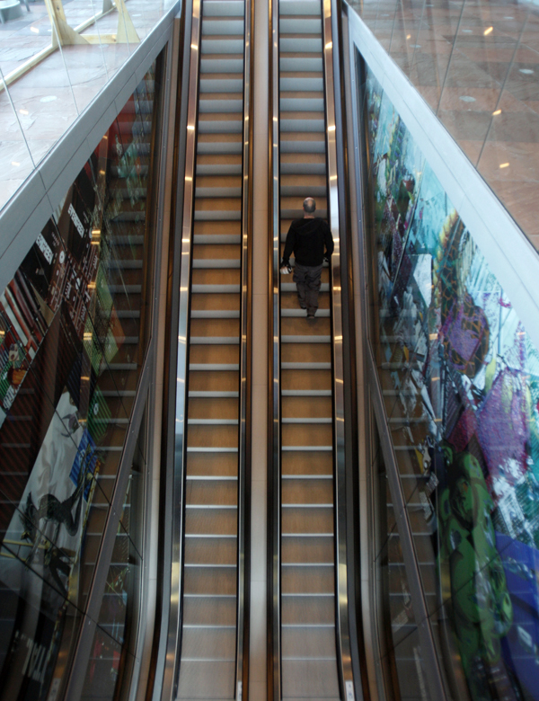 A visitor rides an escalator past artworks at the MAS Museum in Antwerp, Belgium.