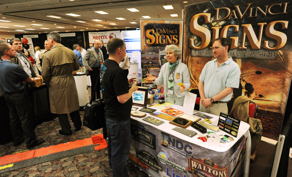 DaVinci Signs of Hermon co-owner Jeanne Savoy, center, and employee Adam McDonald ,right, talk with ink and toner cartridge salesman Jake Ainsworth of Bradford at the Bangor Chamber of Commerce Business Expo at the Bangor Civic Center on Tuesday.