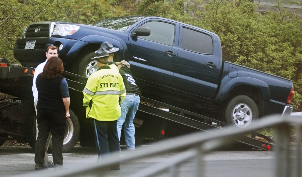 Massachusetts State Police officers stand by as a Toyota pickup truck is placed on a tow truck in a rest area along Interstate 495 in Chelmsford, Mass., Wednesday, May 18, 2011.  Authorities had been searching for a blue Toyota pickup truck seen near where the body or a little boy was found Saturday in South Berwick, Maine.