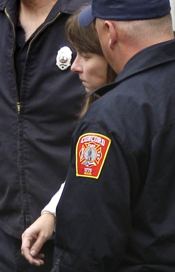 A woman is escorted by emergency workers from the Mass. State Police barracks in Concord, Mass., on Wednesday.