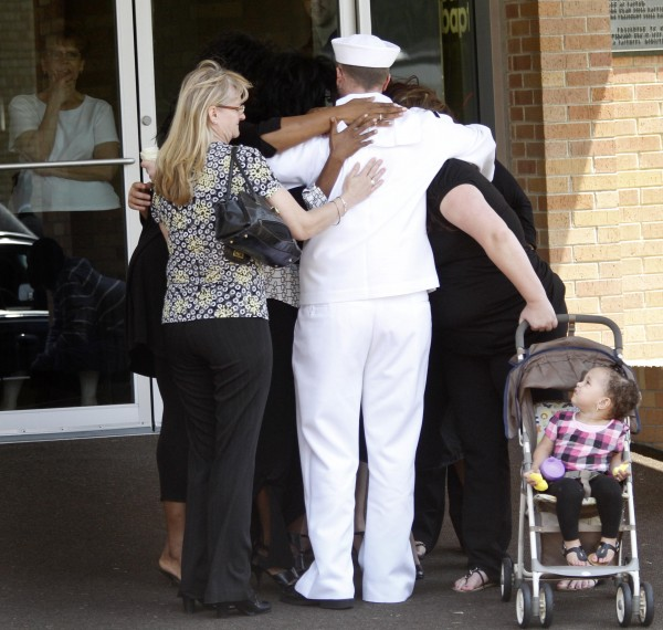 Ian McCrery, dressed in his Naval uniform, is given hugs after the memorial service for his younger brother, Camden Hughes, held  Saturday at Calvary Baptist Church in Grand Prairie, Texas. Camden's mother, Julianne McCrery, of Irving, Texas, is being held without bail on second-degree murder charges in New Hampshire, where she is accused of killing her young son and then dumping his body in Maine on May 14.