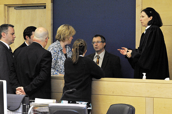 Justice Michaela Murphy (right), confers with defense attorneys, prosecutors and court staff during a sidebar discussion and at the start of defendant Zachary Carr's hearing at Penobscot Judicial Center Friday.