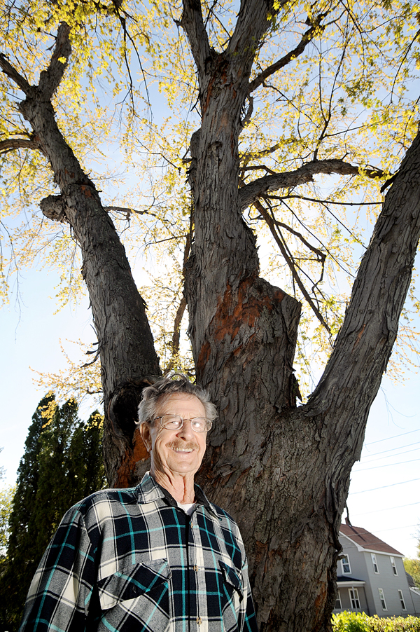 "Rosaire Dumond picked up two pails of bark after lightning struck the silver maple in his backyard on Spring Street in Lewiston on Saturday. ""I was looking out the window and pow, a great ball of fire engulfed the tree."", he said. ""I could not believe my eyes. We have lived here for 46 years and I have seen nothing like it."" Dumond lives in the 100-year-old house with his wife, Robertine."