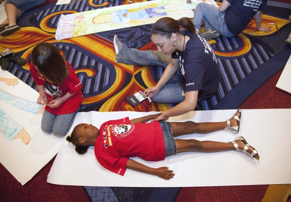 "In this photo taken Friday, May 27, 2011, Mentor Tylesa Fernandez, of Andrews Air Force Base, Md., works with seven year-old Jireh Fraise, of New Orleans, La., during ""Good Grief Camp"" in Arlington, Va., where nearly 500 children of fallen military members take part in activities with volunteer mentors on coping with grief and loss. More than 4,300 children of U.S. troops killed in the Iraq and Afghanistan wars are growing up. Those interviewed at the camp, organized by the nonprofit Tragedy Assistance Program for Survivors every Memorial Day weekend, described it as one outlet that's allowed them to learn to work through their feeling."