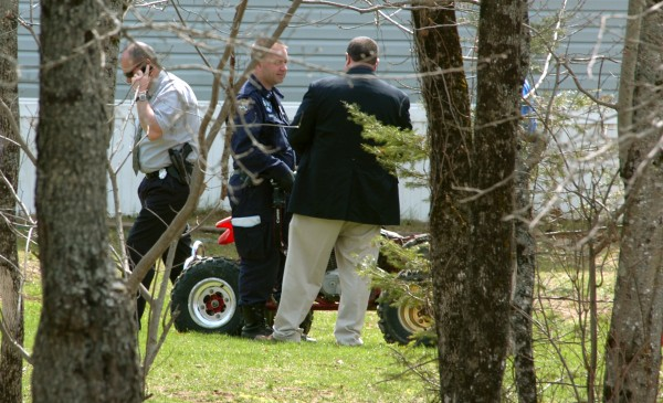 Returning to the scene of a Sunday shooting that left Ryan Mayo, 20, dead, Maine State Police detectives confer as they consider evience near a red ATV on the lawn of 155 French Road in Dover-Foxcroft early May 2. Mayo was shot in the head and killed on May 1. Mayo's brother, Steven, 22, was arrested and charged with murder on Thursday, May 12.