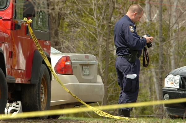 Returning to the scene of a Sunday shooting that left one man dead, Maine State Police detectives confer as they consider evidence around a red ATV on the lawn of 155 French Road in Dover-Foxcroft early Monday. A half dozen investigators were on scene taking photographs, surveying the site and collecting evidence.