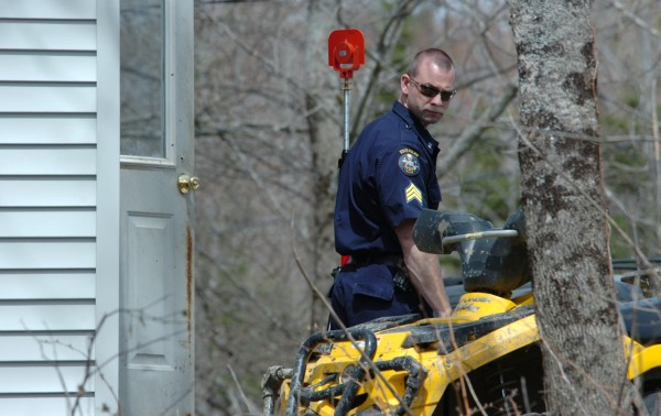 A Maine State Police investigator helps survey the scene Monday of a Dover-Foxcroft shooting that left one man dead Sunday night on the French Road.  A half dozen investigators were on scene taking photographs, surveying the site and collecting evidence.