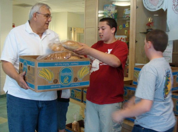 Michael Noonan (center) and Dakota White, both sixth-grade pupils at Ridge View Community School in Dexter, filled a box held by Douglas Vigue of the Dexter Community Food Closet on Tuesday with loaves of homemade bread. Pupils in grade four through seven made the bread with help from King Arthur flour company, and they donated more than 200 loaves to the closet.