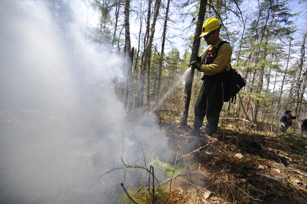 With water pumped from nearby Crocker Pond, Thomas Liba, Helitack Coordinator with the Maine Forest Service, puts out the fire at a simulation burn site during their demonstration for the media in Township 32 MD Monday morning, May 2.