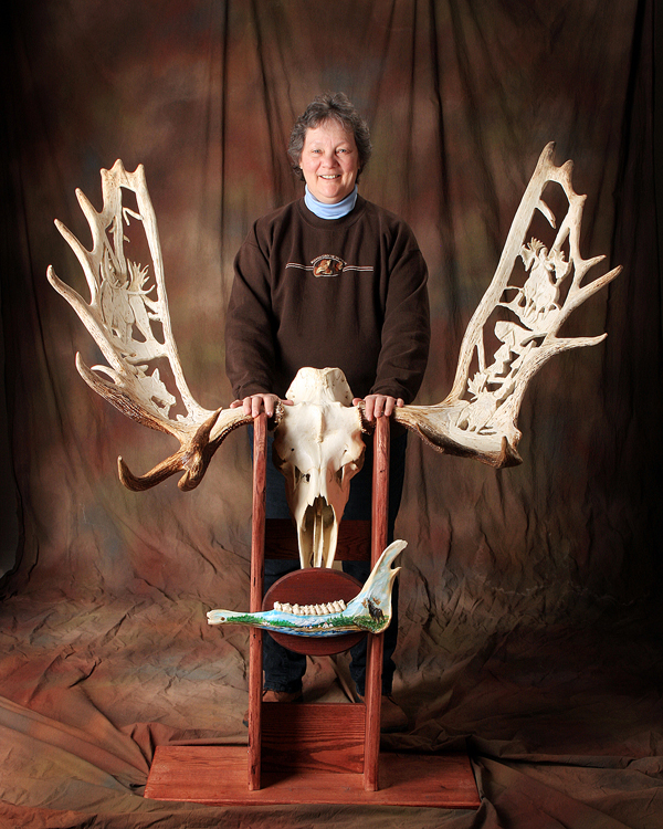 "Georgette Kanach of Gray stands behind ""Forever the Ancient One,"" a moose which she shot and then carved for several years. She completed it for this year's State of Maine Sportsman's Show in March."