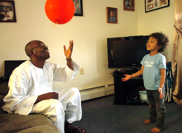 Mama Sora, left, a native of Mali, tosses a ballon around as he plays with his four-year-old son Kenyon in their Bangor home on Tuesday. Sora, who arrived alone in Bangor at age 19 without knowing English, will be receiving his MBA degree from Husson University on Saturday.
