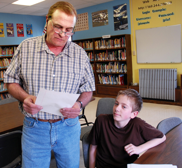 Woodland Consolidated School's grade seven teacher David Sterris checks over a handwriting sample by Richard Schmitt Jr. Schmitt was just named the Zanner-Blosser Grand National Grade Seven Handwriting Champion.