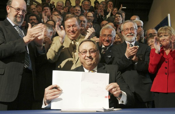 Maine Gov. Paul LePage holds up the health insurance overhaul bill that he just signed at a State House signing ceremony in Augusta, Maine on  Tuesday, May 17, 2011. LePage is surrounded by fellow Republicans, at left is House Speaker Robert Nutting, R-Oakland and Senate President Kevin Raye, center, R-Perry.
