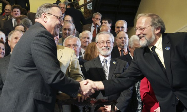 Maine Gov. Paul LePage, left, is congratulated by Rep. Paul Waterhouse, R-Bridgton, right, after signing the health insurance overhaul bill at a State House signing ceremony in Augusta, Maine on  Tuesday, May 17, 2011. LePage is surrounded by fellow Republicans.
