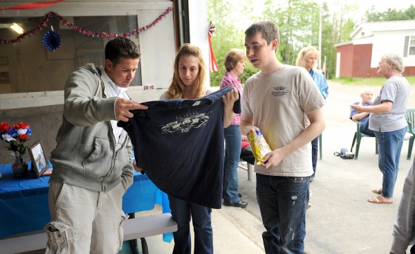 Sgt. Raymond Christie of San Diego, California, (left), Jenn Buzzell look at a T-shirt that was given to Jeffrey Buzzell, 16, (right) by Dale Ernhart Jr. Jeffrey suffers from Alport Syndrome a desease that effected his kidney function and eventually had a kiddney transplant that was donated by his sister Jenn.  Raymond saw a television segment about Jeffrey while serving in the Army in Afghanistan and the two became friends on Facebook.  Raymond returned to the U.S. three weeks ago and he came to meet Jeffrey in Maine as soon as he was able to find time.