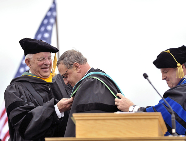 Gov. Paul LePage (center), receives an honorary doctorate for public service from Husson University President Robert Clark (right), and trustee Dick Trott (left), in Bangor, Saturday. LePage, who was homeless as a boy, said his life changed when he attended the school with assistance, which then was called Husson College.