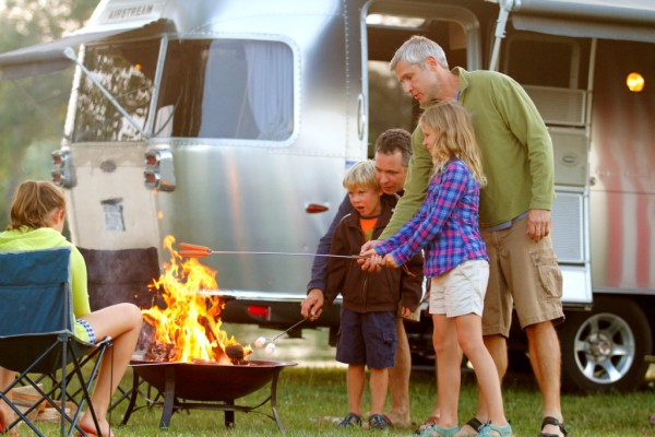 A family cooks hot dogs over an open fire near their Airstream trailer.