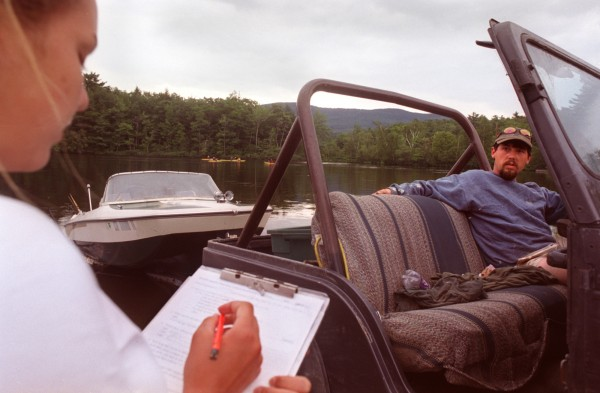 At Megunticook Lake in 2002, Amelia Fiske (left), a volunteer working with the Megunticook Watershed Association, asks boat owner Brad Wellman of Camden questions in a survey about invasive plants. The association and others like it around the state are concerned with the spread of Milfoil, an invasive plant that can be easily transmitted from an infected lake to an uninfected lake if boats are not cleaned properly.