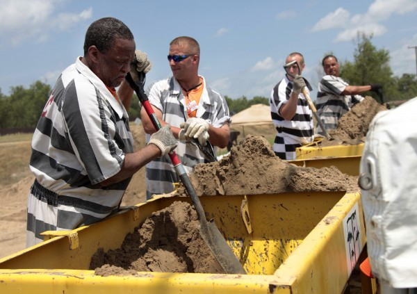 Inmate trustees from St. Martin Parish Correctional Center make sandbags for residents in Stephensville, La., on Wednesday in preparation for impending flooding from the likely diversion of Mississippi River floodwaters into the Atchafalaya Basin.