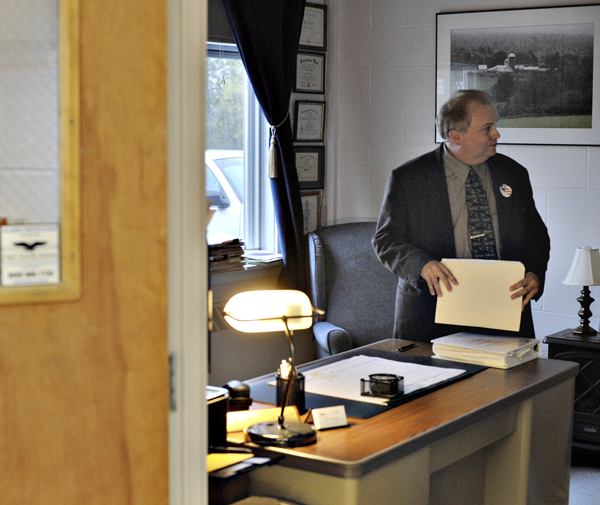 Town manager Rick Briggs cleans out his office after resigning at a selectmen's meeting Thursday night at the former Newburgh Elementary school, now the town office.