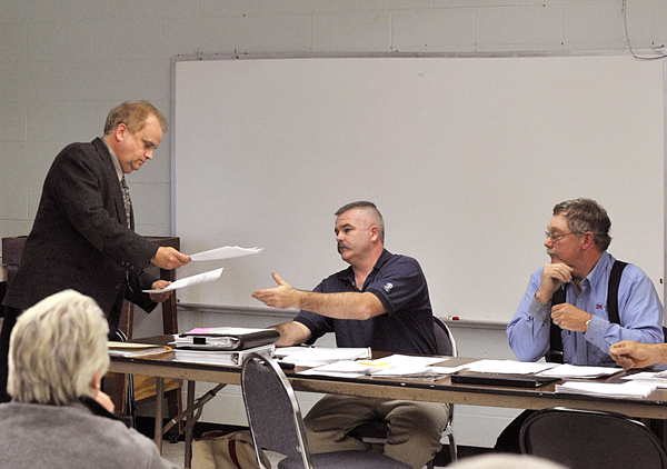 Town manager Rick Briggs hands in his resignation to selectman Mike Burns at a public meeting held Thursday night at the former Newburgh Elementary school, now the town office.