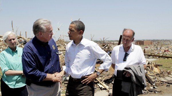 President Barack Obama (center) shakes hands with Missouri Gov. Jay Nixon (second from left) as they visit tornado victims in Joplin, Mo., on Sunday, May 29, 2011. At far left is Georganne Wheeler Nixon, wife of the governor. At far right is Joplin Mayor Mike Woolston.