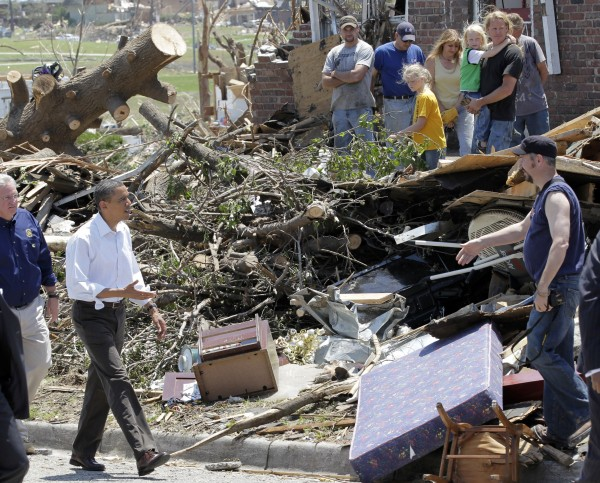 President Barack Obama, followed by Missouri Gov. Jay Nixon, views damage and greets residents from the tornado that devastated Joplin, Mo., on Sunday, May 29, 2011.