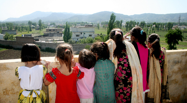 Pakistani children look out from their high vantage point, to see the compound of Osama bin Laden in Abbottabad, Pakistan, on Tuesday after a U.S. military raid late Monday.