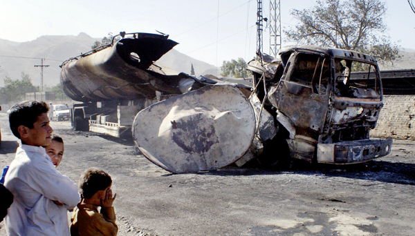 Pakistani youngsters stand next to a burnt NATO oil tanker caused by alleged militants attacked in Landi Kotal near Afghan border in Pakistan on Saturday. A tanker carrying oil for NATO forces in Afghanistan exploded Saturday in northwestern Pakistan as people tried to siphon off some of its fuel, and 15 were killed, an official said.
