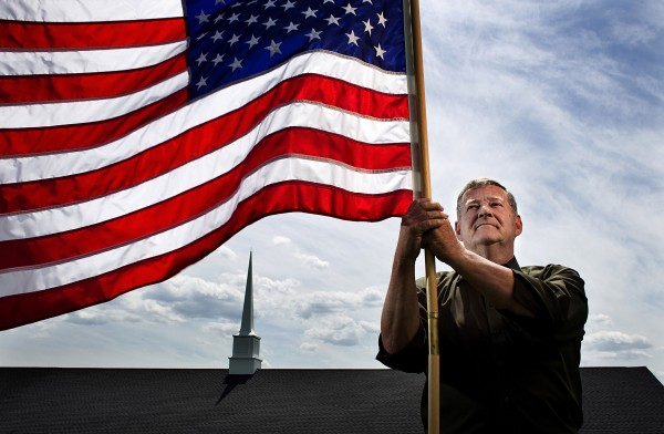 Bob Moats, a Pastor at The Christian Bible Fellowship church in Newville, Penn., holds a flag last week.