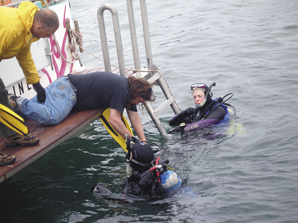 Tour boat operator and scuba enthusiast Ed Monat assists two scuba divers Saturday who were participating in an annual harbor clean-up event in Bar Harbor. A dozen divers spent several hours Saturday pulling up unnatural debris from the harbor floor.
