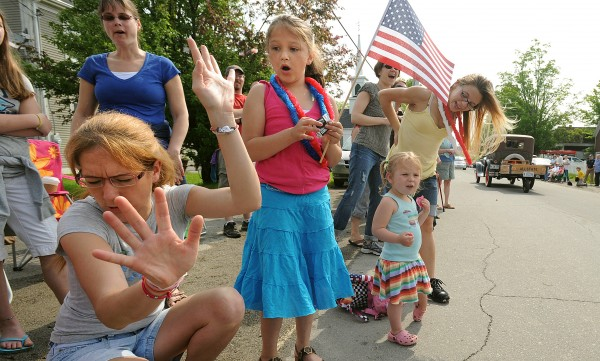 Jill O'Brien of Belmont (left) shields herself from some candy that was being tossed from a vehicle in the Memorial Day parade in Searsmont Monday morning. O'Brien and her daughter Maddison, 7, (second from left) come to the parade every year.