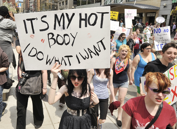 "Women march through downtown Boston during the ""SlutWalk"" in Boston, Mass., Saturday which organizers described as a demonstration against those who blame the victims of sex crimes. The walk was held in response to a Toronto police officer who said women shouldn't dress like ""sluts"" if they wanted to avoid being raped."