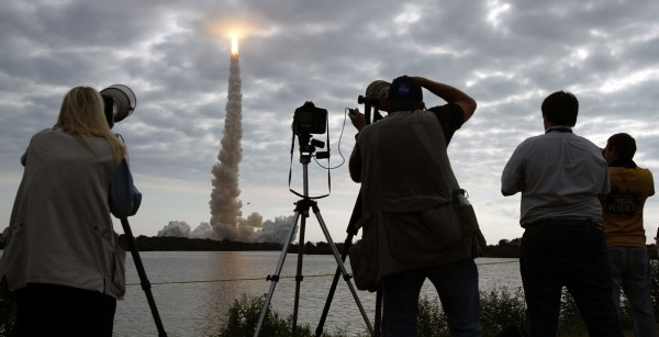 Photographers capture space shuttle Endeavour as it pierces the clouds and disappears after launch at Cape Canaveral, Fla., on Monday, May 16, 2011.