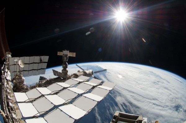 The sun, a portion of the International Space Station and Earth's horizon are featured in this image photographed by a spacewalker, using a fish-eye lens during the fourth spacewalk Friday.