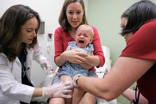 Duncan Barnes, 1, being held by his mother Jennifer Barnes, reacts while receiving vaccine for swine flu from Dr. Susan Henderson, left, and a vaccine for seasonal flu from nurse Allison Ross during a swine flu vaccination clinical trial for children at Emory Children's Center Sept. 2 in Atlanta.