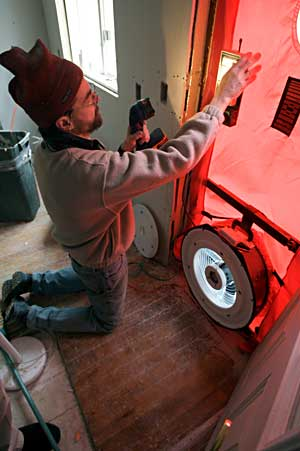 "Al Heath performs a blower door test in March 2010 to gauge a house's air tightness. Heath, a nurse practitioner and energy consultant, completed ""green"" restoration of a World War II-era duplex in Bath."